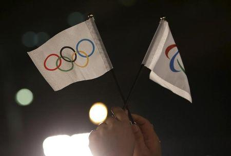 A spectator waves Olympic and Paralympic flags during an unveiling event for the Tokyo 2020 Olympic and Paralympic games emblems at Tokyo Metropolitan Government Building in Tokyo
