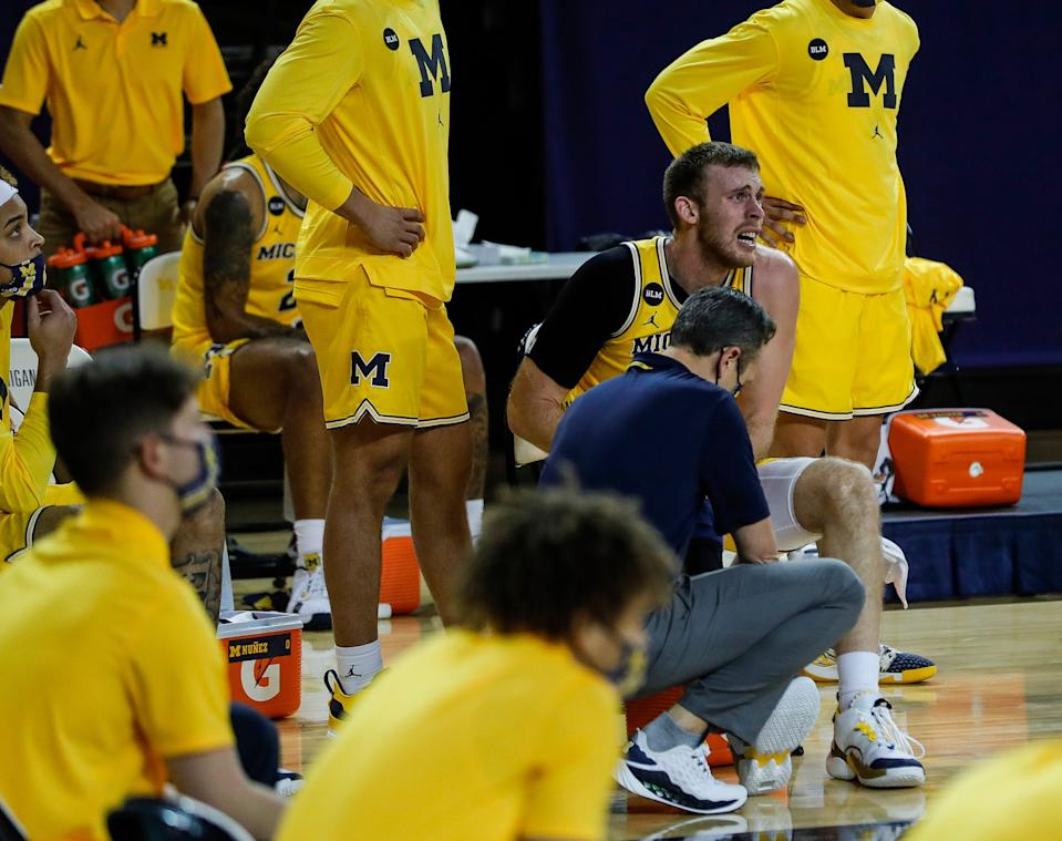 Michigan forward Austin Davis is checked for his leg injury by a trainer during the second half against Toledo at Crisler Center in Ann Arbor, Wednesday, Dec. 9, 2020.