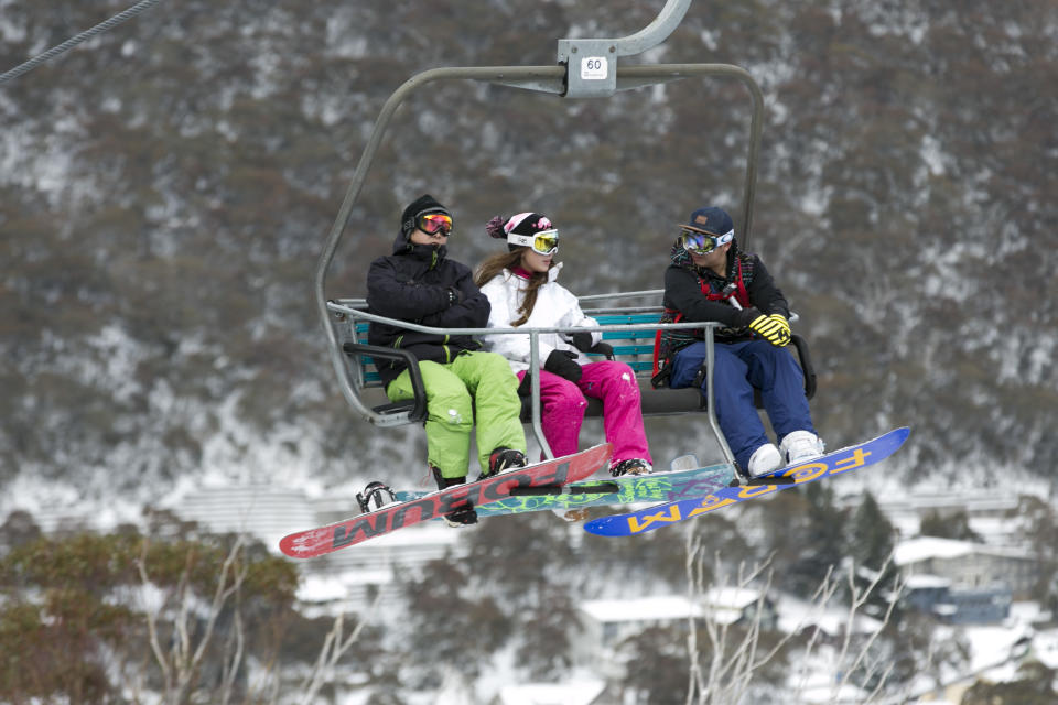 Three skiers on a chairlift at Thredbo, NSW