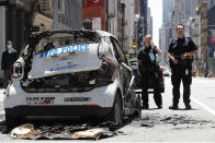 Officers stand guard beside a burned-out mini-New York Police Department vehicle, abandoned on Broadway in Lower Manhattan, Sunday, May 31, 2020, in New York, following a night of unrest and protests over the death of George Floyd, a black man who was in police custody in Minneapolis. Floyd died after being restrained by Minneapolis police officers on May 25. (AP Photo/Kathy Willens)