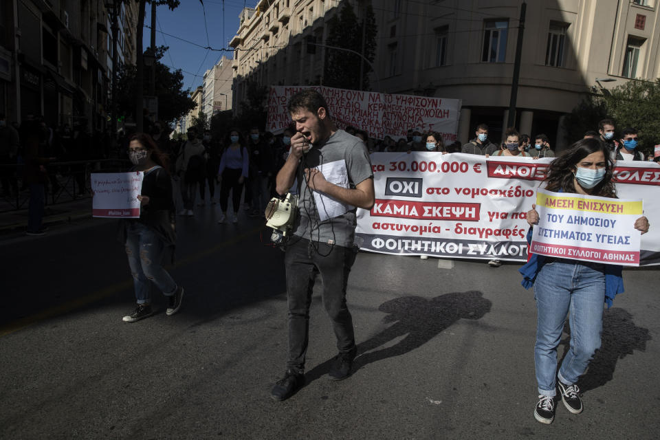 """University students wearing face masks to protect against coronavirus, chant slogans as they carry a banner that read """"Not to the bill"""" during a rally against education reforms in Athens, Thursday, Feb. 4, 2021. Thousands of protesters in Greece have held demonstrations in the Greek capital and the second largest city of Thessaloniki against plans by the government to police university campuses. (AP Photo/Petros Giannakouris)"""