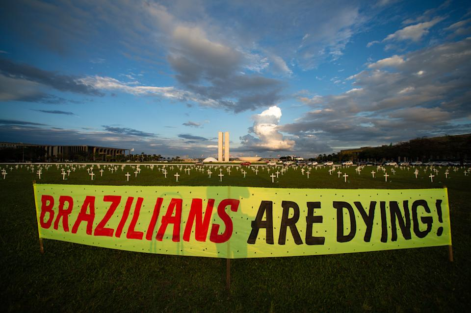 BRASILIA, BRAZIL - APRIL 27: A banner with the message 'Brazilians are dying' is displayed near the 400 crosses placed in honor of the almost 400,000 victims of coronavirus (COVID-19) pandemic at brazilian Congress on April 27, 2021 in Brasilia, Brazil. According to the last official reports, released on  Monday 26, Brazil registers 391,936 victims of COVID-19. With an average of around 2,500 deceases per day, the country expects to reach 400,000 victims this week. Today, Brazilian Congress opened an inquiry into Bolsonaro's COVID handling. (Photo by Andressa Anholete/Getty Images)