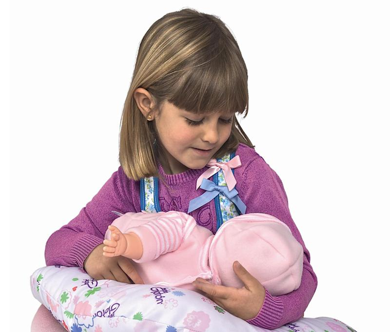 This product image released by Berjuan Toys shows  a girl playing with The Breast Milk Baby doll. The breastfeeding doll, whose suckling sounds are prompted by sensors sewn into a halter top, has caught some flak after hitting the U.S. market. (AP Photo/Berjuan Toys)