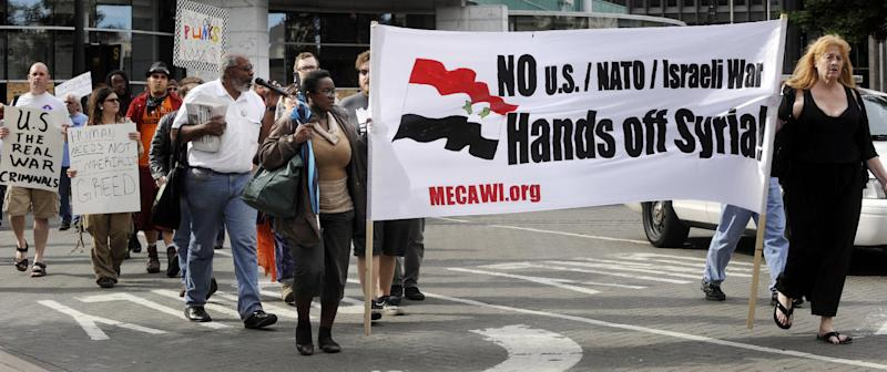 In a Sept. 8, 2013 file photo, protestors peacefully demonstrate in Detroit against the impending attack on Syria. Members of the Michigan Committee for Emergency War and Injustice were among the marchers. The question of whether the U.S. military becomes involved in Syria's civil war weighs heavily on the minds of U.S. Syrians and other Arabs. But divisions among them have been building for a long time. (AP Photo/The Detroit News, Charles V. Tines)