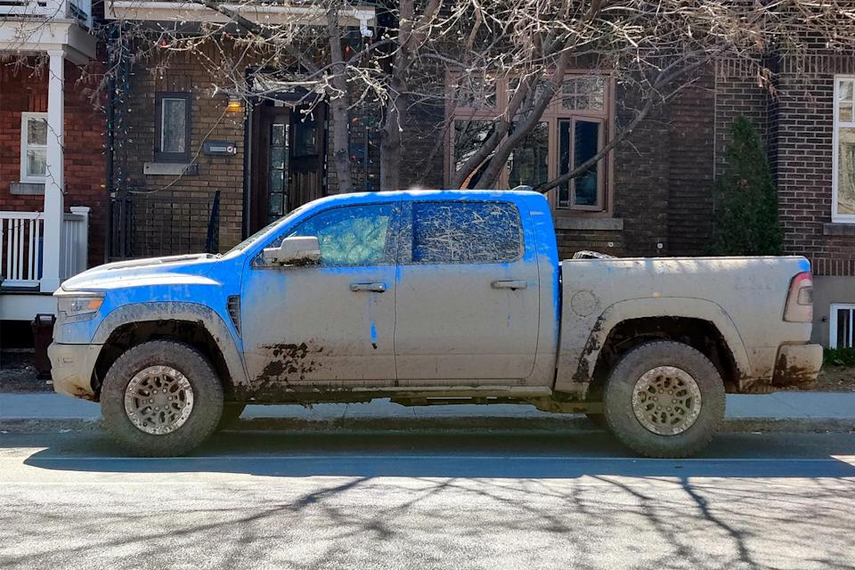 A blue 2021 Ram 1500 TRX pickup truck covered in mud parked on a city street