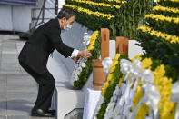 Japan's Prime Minister Yoshihide Suga offers a wreath in front of the cenotaph dedicated to the victims of the atomic bombing at the Hiroshima Peace Memorial Park in Hiroshima, western Japan Friday, Aug. 6, 2021. Hiroshima on Friday marked the 76th anniversary of the world's first atomic bombing of the city. (Kyodo News via AP)