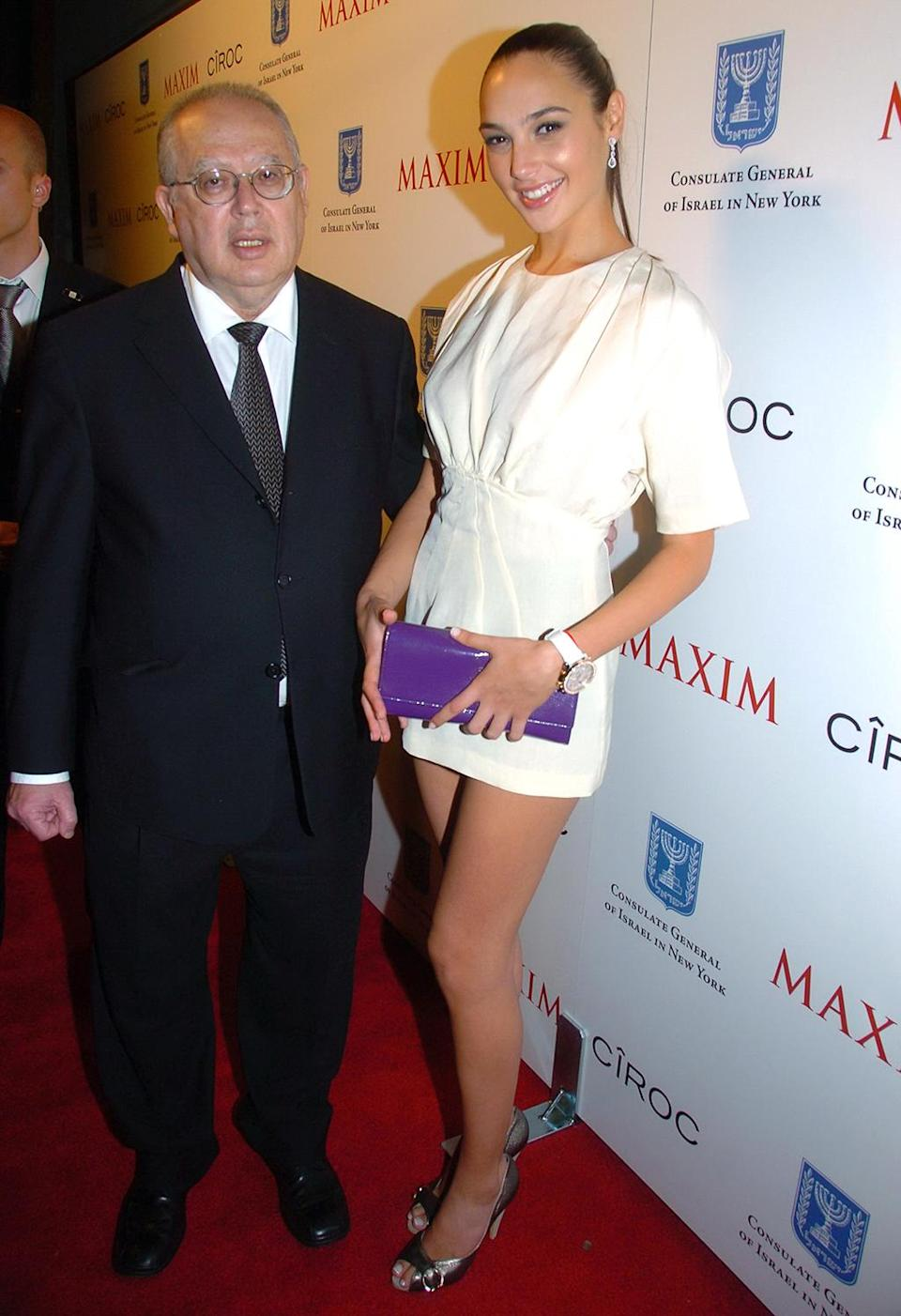 """<p>After serving two years in the Israel Defense Forces, the 21-year-old took part in a Maxim photo shoot titled """"Women of the Israeli Army."""" The former Miss Israel posed with Israeli Ambassador Arye Mekel at the issue's celebration in New York on June 19, 2007. (Photo: John Roca/Getty) </p>"""