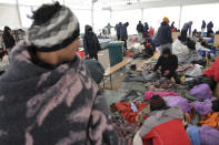Migrants sit in a temporary shelter at the Lipa camp northwestern Bosnia, near the border with Croatia, Saturday, Dec. 26, 2020. Hundreds of migrants are stranded in a burnt-out squalid camp in Bosnia as heavy snow fell in the country and temperatures dropped during a winter spell of bad weather after fire earlier this week destroyed much of the camp near the town of Bihac that already was harshly criticized by international officials and aid groups as inadequate for housing refugees and migrants.(AP Photo/Kemal Softic)