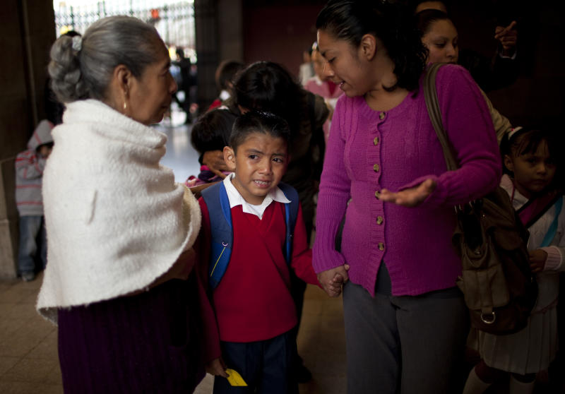 "Diego Angel is consoled by his mother Dulce Castro, right, and grandmother Margarita as he is escorted to the first day of classes in Mexico City, Monday, Aug. 19, 2013. Mexican children returned to classrooms Monday, and they were getting a quick lesson: Not just school kids make mistakes. Their brand new textbooks have the kinds of errors that they are supposed to be learning not to make: words written with a ""c'' instead of an ""s,"" too many commas, not enough accents and at least one city located in the wrong state. (AP Photo/Ivan Pierre Aguirre)"