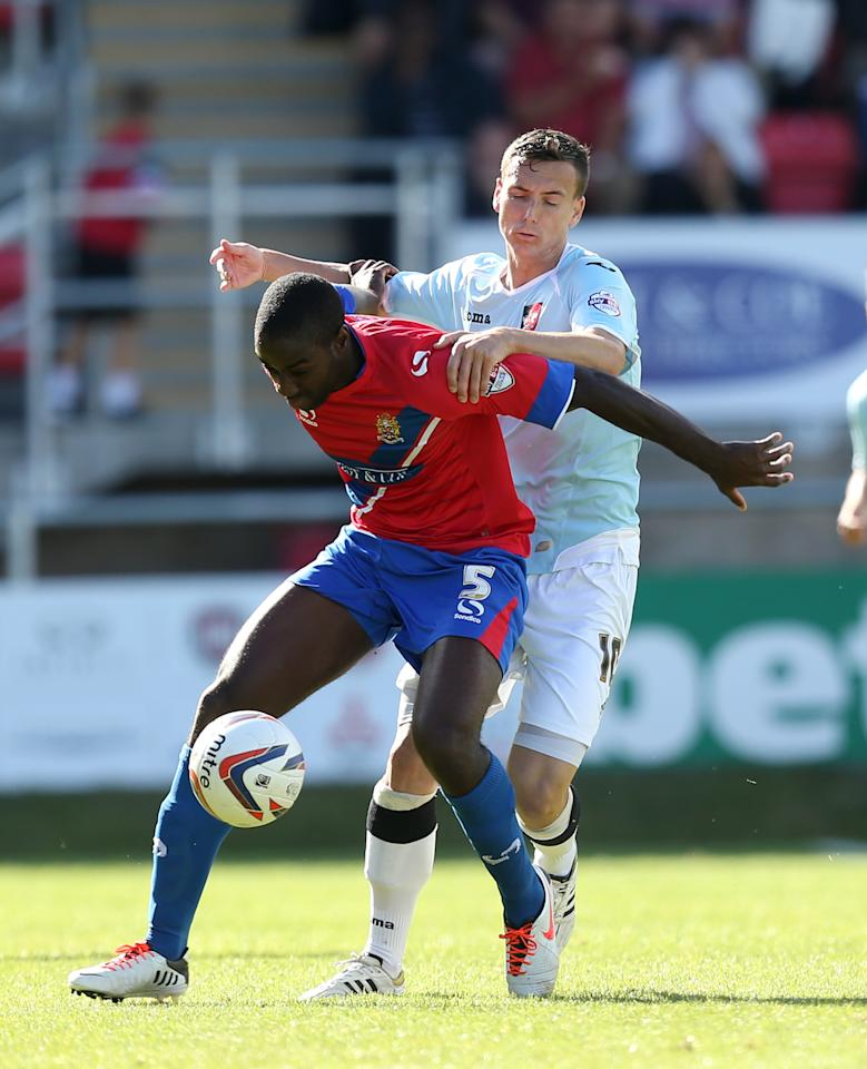 Dagenham & Redbridge's Brian Saah (left) and Exter City's Alan Gow battles for possession of the ball during the Sky Bet Football League Two match at the London Borough of Barking and Dagenham Stadium, London.