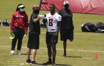 Atlanta Falcons' Kyle Pitts, center, talks with a coach during an NFL football rookie minicamp on Friday, May 14, 2021, in Flowery Branch, Ga. (AP Photo/Brynn Anderson)