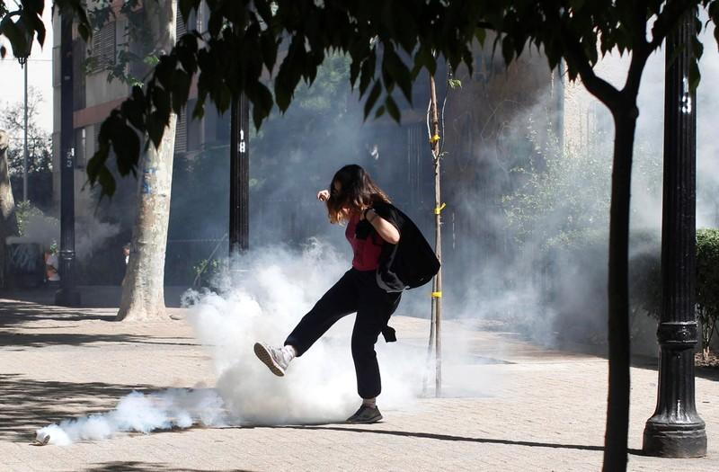 A demonstrator kicks a tear gas canister during a protest against the increase in the subway ticket prices in Santiago