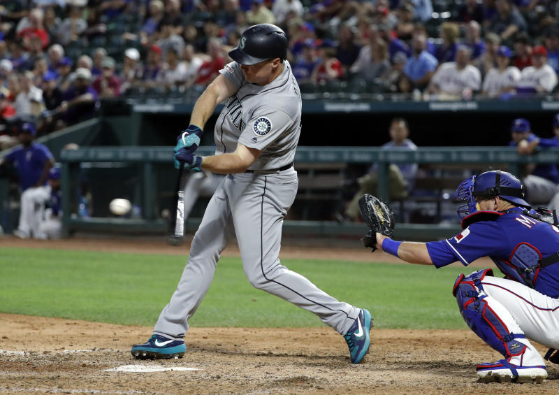 Seattle Mariners' Jay Bruce hits an RBI sacrifice fly as Texas Rangers catcher Isiah Kiner-Falefa watches during the seventh inning of a baseball game in Arlington, Texas, Tuesday, May 21, 2019. (AP Photo/Tony Gutierrez)