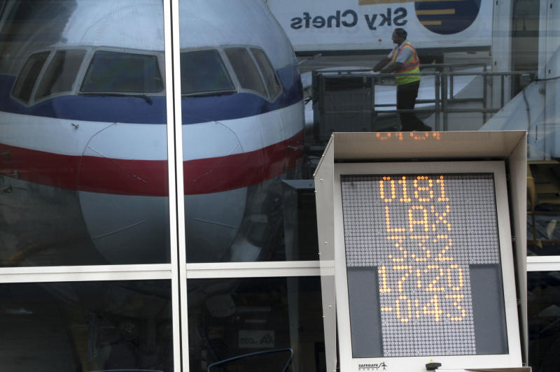 In this Wednesday, Aug. 1 2012 photo, a countdown to departure clock is framed by a reflection of an American Airlines fleet clerk servicing an airplane at JFK International airport in New York. Travelers still have to put up with packed planes, rising fees and unpredictable security lines, but they are missing fewer business meetings or chances to tuck their kids into bed. Nearly 84 percent of domestic flights arrived within 15 minutes of their schedule time in the first half of the year, the best performance since the government started tracking such data in 1988. (AP Photo/Mary Altaffer)