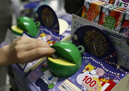 Office worker puts a 100 yen coin into a frog-shaped piggy bank filled with snacks for office workers, Ezaki Glico's kiosks-in-a-box Office Glico, at an office in Tokyo