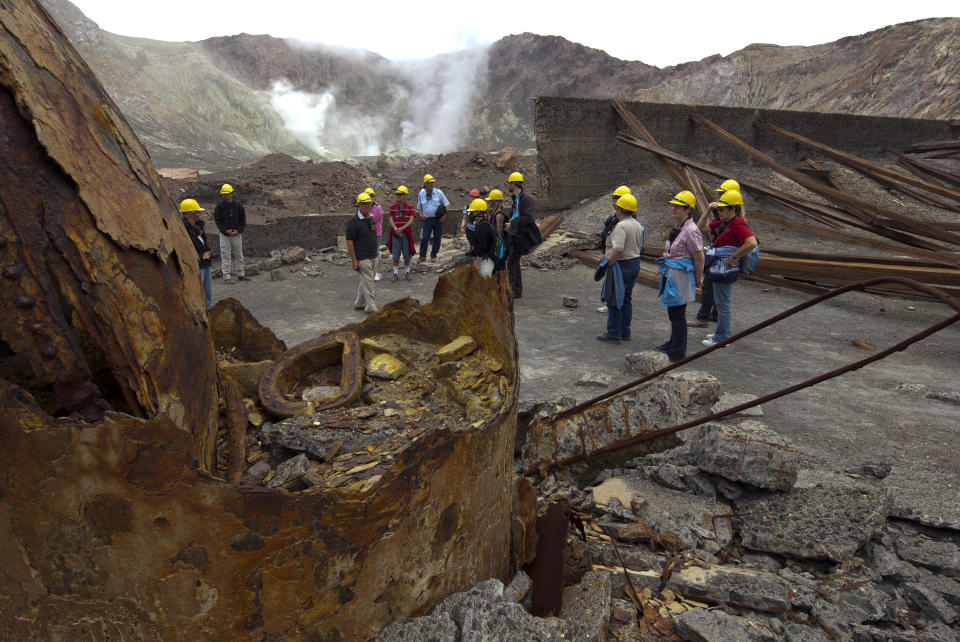 Tourists exploring the inner crater of New Zealand's only active marine volcano White Island look at the remains of buildings from old mines.