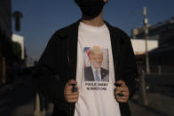 """Jude Hensley, 17, pauses for photos in a T-shirt to express his displeasure with President Donald Trump on Wednesday, Oct. 28, 2020, in Los Angeles. """"Trump is a fascist, and he does not deserved to be the President of our country,"""" said Hensley who is not eligible to vote due to his age. (AP Photo/Jae C. Hong)"""