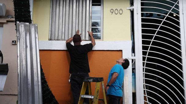 PHOTO: Workers place hurricane shutters over a window as they help prepare a business for the possible arrival of Hurricane Dorian on Aug. 30, 2019, in Miami Beach, Fla. (Joe Raedle/Getty Images)