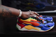 In this July 8, 2021, photo Latrice Felix places her hand on the last sneakers her son Alan Womack Jr. wore before he was killed in 2020 during a fight, in King of Prussia, Pa. (AP Photo/Matt Rourke)