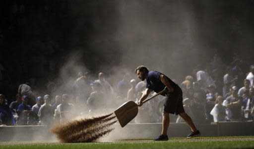 With half of the Wrigley Field lights out a member of the grounds crew prepares the infield after a rain delay for a baseball game between the Chicago Cubs and the Los Angeles Dodgers Monday, June 18, 2018, in Chicago. (AP Photo/Charles Rex Arbogast)