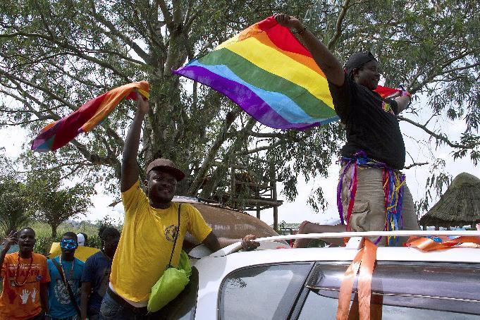 People wave rainbow flags at a gay pride rally after the overturning of anti-homosexuality laws in Entebbe, on August 9, 2014 (AFP Photo/Isaac Kasamani)