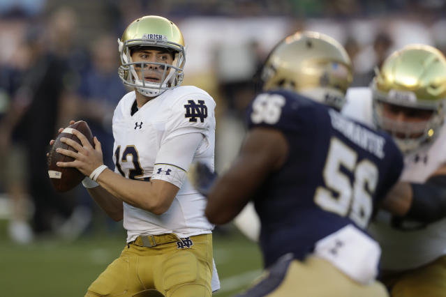 Notre Dame quarterback Ian Book (12) looks to throw a pass during the first half of an NCAA college football game against Navy, Saturday, Oct. 27, 2018, in San Diego. (AP Photo/Gregory Bull)