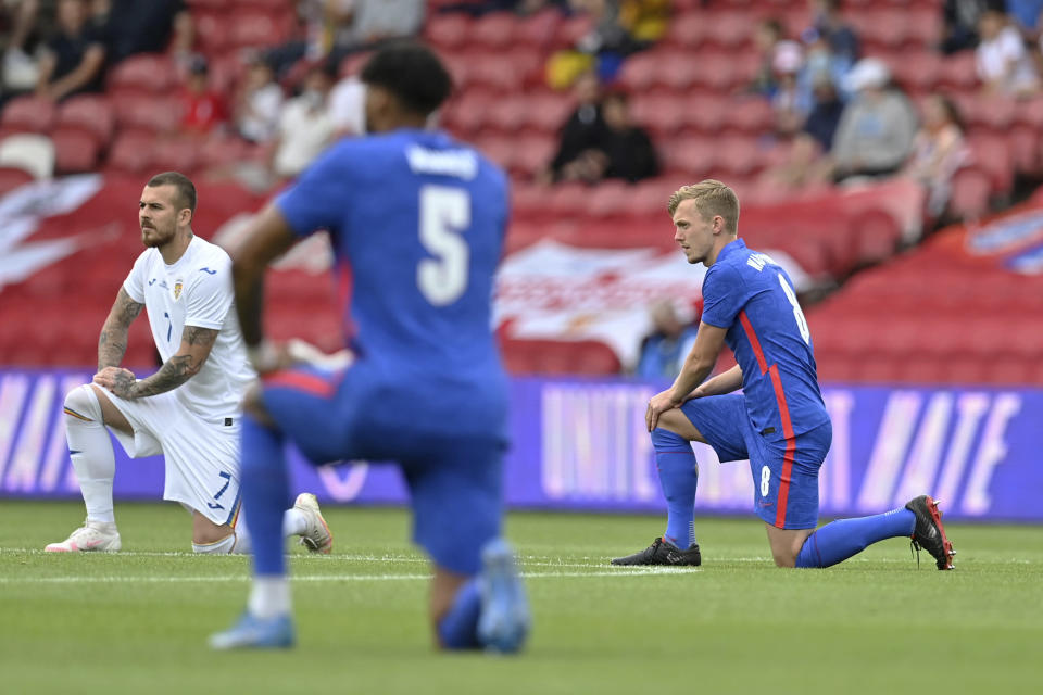 England's and Romania's players take a knee before the international friendly soccer match between England and Romania in Middlesbrough, England, Sunday, June 6, 2021. (Paul Ellis, Pool via AP)