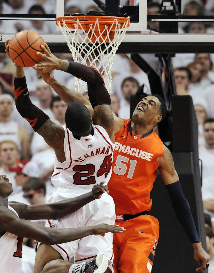Syracuse's Fab Melo, right, attempts to block the shot of Louisville's Chane Behanana during the first half of their NCAA college basketball game, Monday, Feb. 13, 2012, in Louisville, Ky. (AP Photo/Timothy D. Easley)