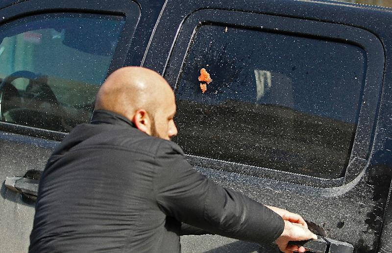 A Palestinian protester throws a tomato at a vehicle containing members of a US economic delegation in Bethlehem on January 30, 2018 (AFP Photo/Musa AL SHAER)