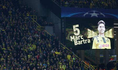 Borussia Dortmund fans look on as a message is displayed in support of Borussia Dortmund's Marc Bartra
