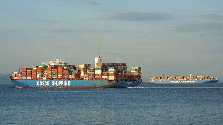 Container ship with COSCO SHIPPING written on hull, another ship in the distance