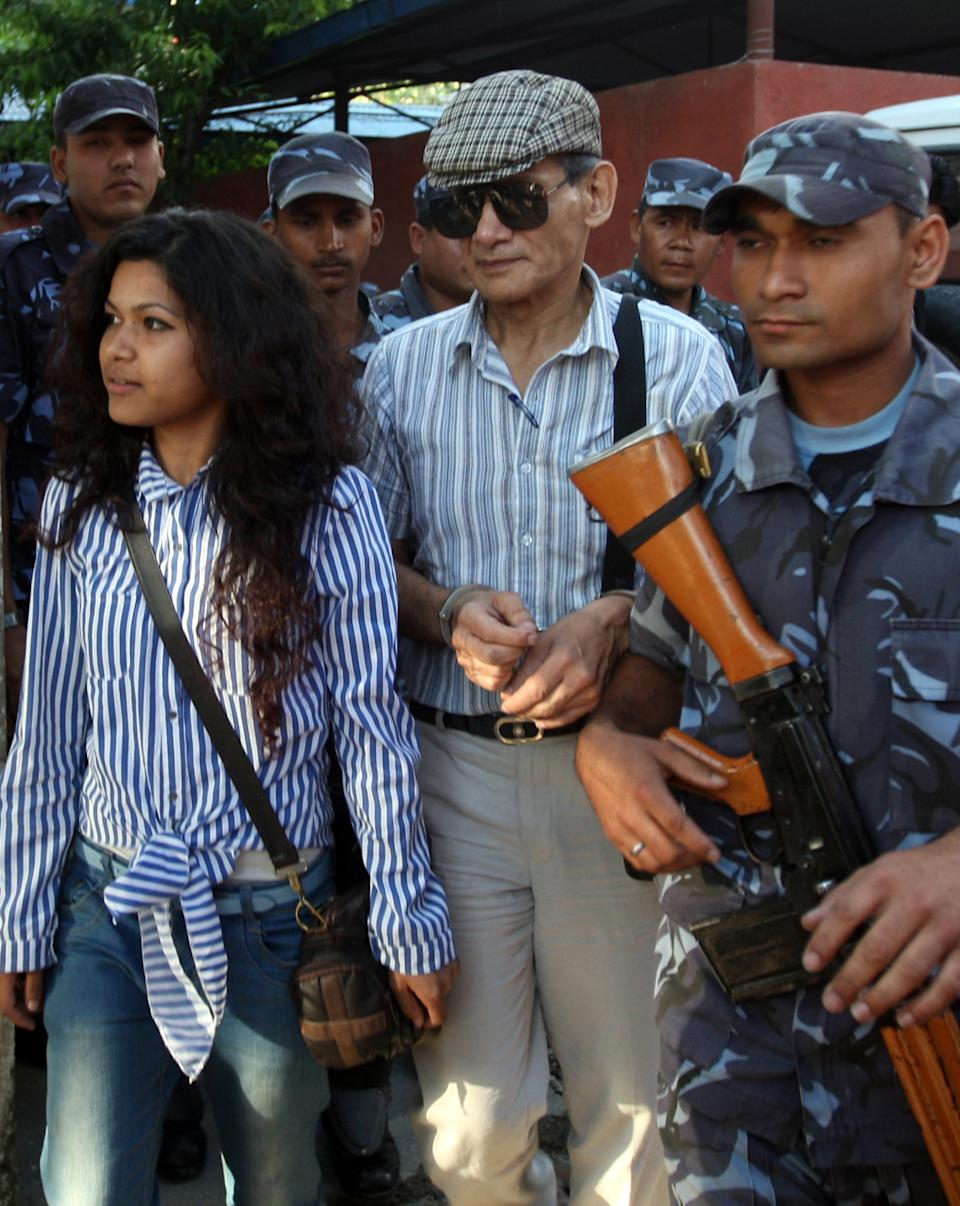 French serial killer Charles Sobhraj (C) and Nihita Biswas (L) who reportedly married with Charles is guided by Nepalese policemen towards a waiting vehicle after a court hearing in Kathmandu on May 31, 2011. Charles Sobhraj, a French citizen who is serving a life sentence in Nepal for the murder of an American backbacker in 1975, has been linked with a string of killings across Asia in the 1970s, earning the nickname