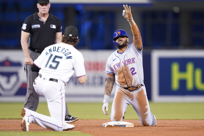 New York Mets' Dominic Smith (2) reacts after hitting a double during the second inning of a baseball game against the Miami Marlins, Wednesday, Aug. 4, 2021, in Miami. At left is Miami Marlins third baseman Brian Anderson (15). (AP Photo/Lynne Sladky)