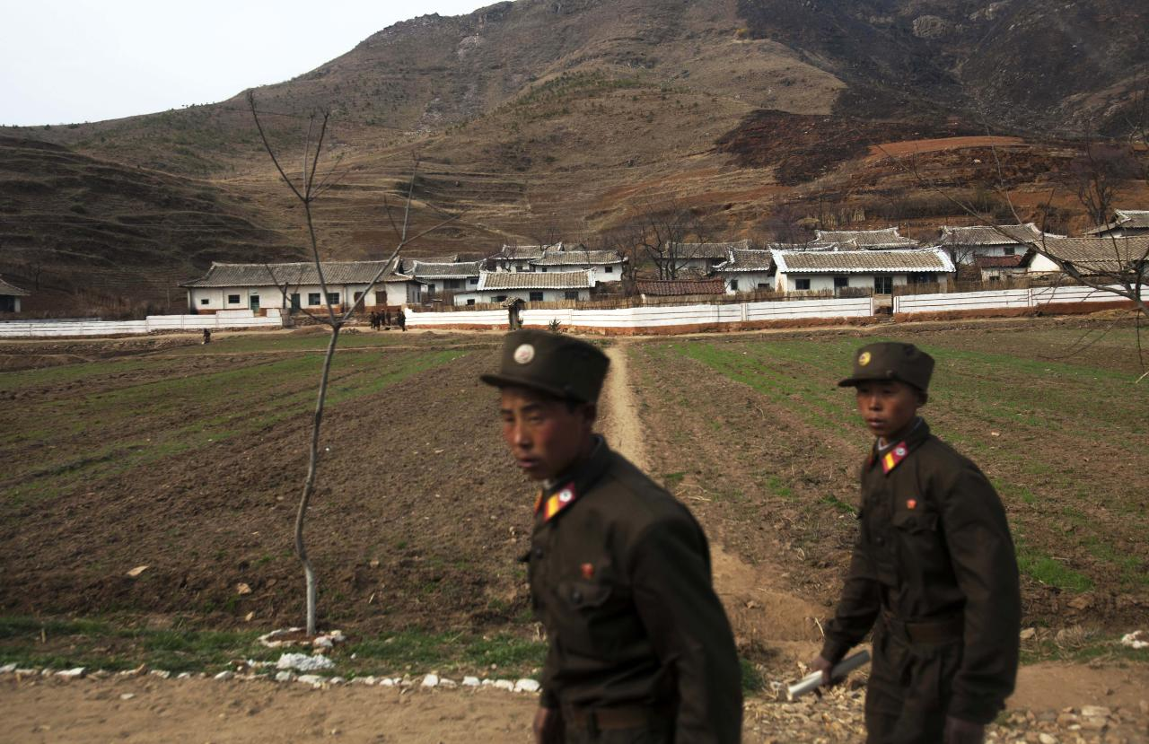 ADVANCE FOR USE SUNDAY, JULY 24, 2011 AND THEREAFTER - In this Tuesday, April 17, 2011 photo, two North Korean soldiers walk along a road and past a small village near the demilitarized zone that separates the two Koreas outside of Kaesong, North Korea. (AP Photo/David Guttenfelder)