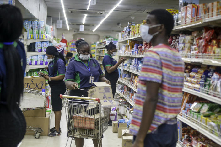 Shop assistants wearing face masks to prevent against the spread of the new coronavirus take stock in a supermarket in Lagos, Nigeria Friday, March 27, 2020. The new coronavirus causes mild or moderate symptoms for most people, but for some, especially older adults and people with existing health problems, it can cause more severe illness or death. (AP Photo/Sunday Alamba)