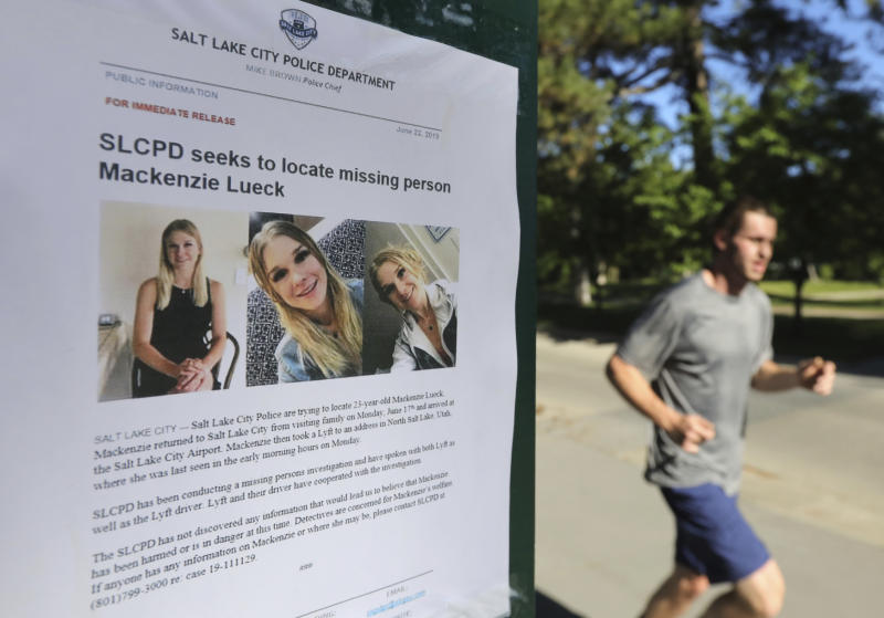 In this June 24, 2019 file photo, a jogger runs pass a poster of Mackenzie Lueck at Liberty Park in Salt Lake City. One person was taken into custody Friday, June 28, in connection with the disappearance of Lueck, a Utah college student who disappeared 11 days ago. | Rick Bowmer—AP
