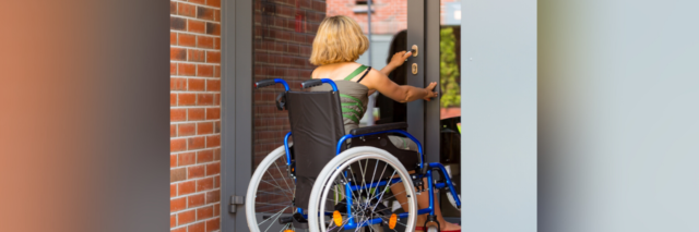 Woman in a wheelchair opening a door.