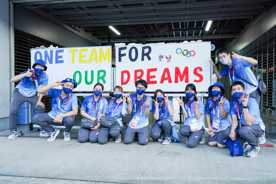 TOKYO, JAPAN - JULY 25: Japanese volunteers with a sign that says one team for our dreams competing on Women's Road Race during the Tokyo 2020 Olympic Games at the Fuji International Speedway on July 25, 2021 in Tokyo, Japan (Photo by Ronald Hoogendoorn/BSR Agency/Getty Images)