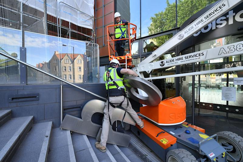 Contractors use an aerial platform outside Bristol music venue Colston Hall to remove the name of 17th century merchant Edward Colston from its signage (PA)