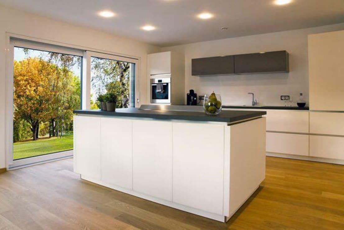 <p>The modern style welcomes us into the kitchen, where adequate legroom has been set up to ensure a most sociable look and feel. And just see how garden views and sunshine continue to flourish indoors via that generous glass door.</p><p>Let's scope out a few more images (and floor plans) of this oh-so stunning creation.</p>  Credits: homify / ADAY GRUP Hafif Çelik Yapılar A.Ş. / LGS CONSTRUCTION