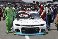 FILE - In this June 22, 2020, file photo, Kyle Busch, left, and Corey LaJoie, right, join other drivers and crews as they push the car of Bubba Wallace to the front of the field prior to a NASCAR Cup Series auto race at the Talladega Superspeedway in Talladega Ala. In an extraordinary act of solidarity with NASCAR's only Black driver, dozens of drivers pushed the car belonging to Wallace to the front of the field before Monday's race as FBI agents nearby tried to find out who left a noose in his garage stall over the weekend. Wallace became just the second Black driver to win at NASCAR's top Cup Series level when rain stopped the playoff race at Talladega Superspeedway, Monday, Oct. 4, 2021. (AP Photo/John Bazemore, File)