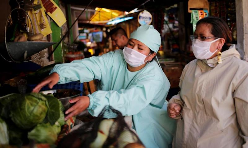 Reina and Cecilia Gutierrez, wearing protective clothing, are seen at a market amid the coronavirus outbreak in La Paz, Bolivia, this month.