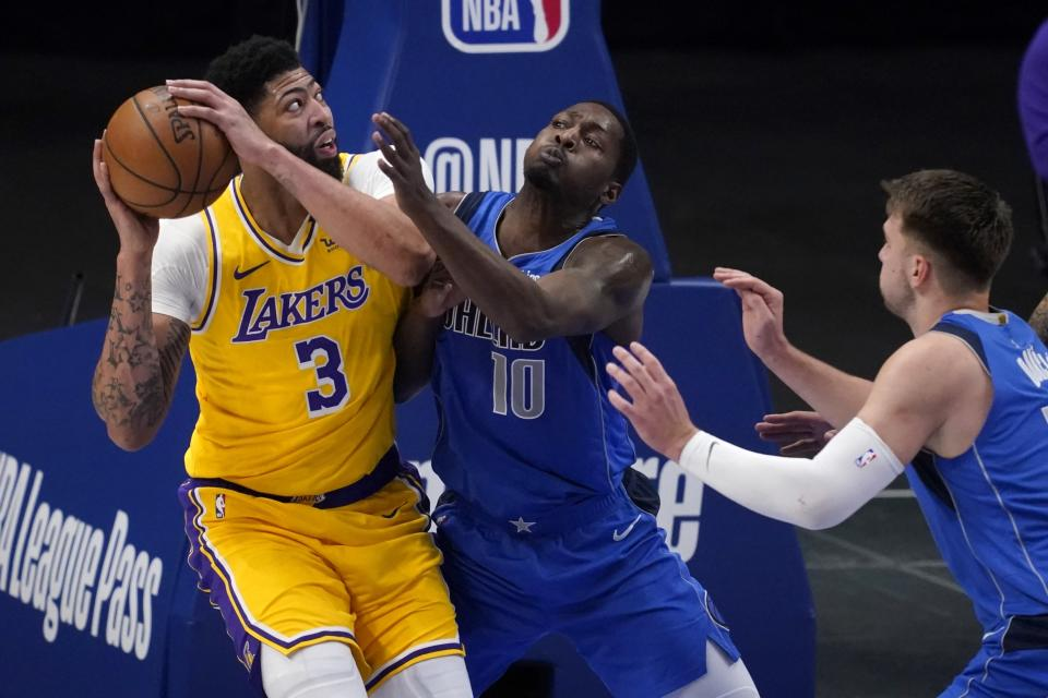 Los Angeles Lakers' Anthony Davis (3) works against Dallas Mavericks' Dorian Finney-Smith (10) and Luka Doncic, right, for a shot in the first half of an NBA basketball game in Dallas, Thursday, April 22, 2021. (AP Photo/Tony Gutierrez)