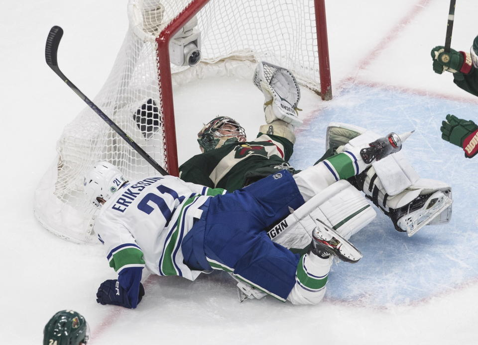 Minnesota Wild goalie Alex Stalock (32) is crashed into by Vancouver Canucks' Loui Eriksson (21) during the second period of an NHL hockey playoff game Thursday, Aug. 6, 2020 in Edmonton, Alberta. (Jason Franson/The Canadian Press via AP)