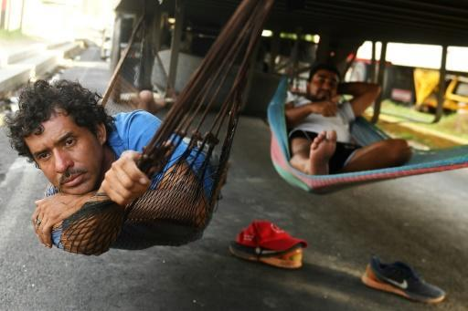 Truck drivers rest under a truck while waiting for protesters to clear a roadblock in Diriamba, 40 kilometers (25 miles) from Managua