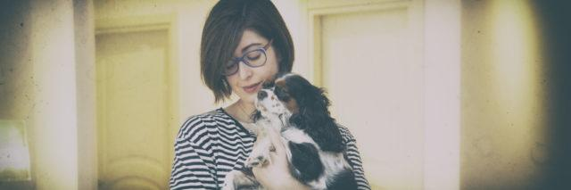 Young woman with Cavalier King Charles Spaniel dog.