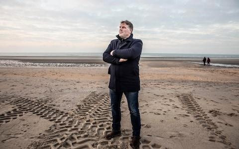 Bram Degrieck, Mayor of De Panne, stood on the beach on the Belgium coast where the first smugglers boat carrying immigrants was seized this week - Credit: Jeff Gilbert