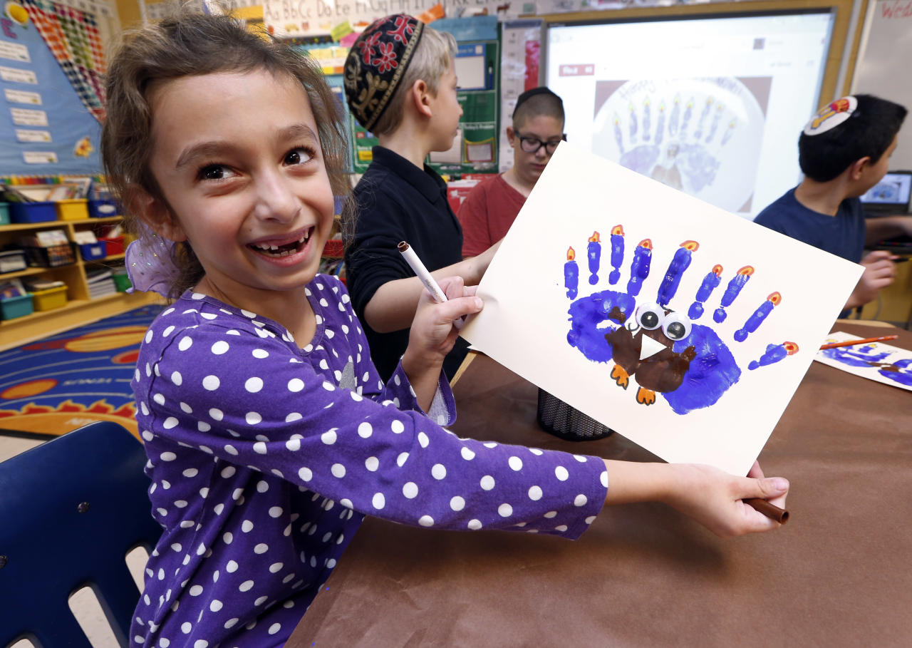 Second-grader Rozie Aronov, 7, holds up a menurkey, a paper-and-paint mashup of a menorah and turkey she created at Hillel Day School in Farmington Hills, Mich., Wednesday, Nov. 20, 2013. The recent class project reflects one way for Jews in the United States to deal with a rare quirk of the calendar that overlaps Thanksgiving with the start of Hanukkah. The last time it happened was 1888 and the next time is 79,043 years from now _ by one estimate that's widely repeated in Jewish circles. (AP Photo/Paul Sancya)