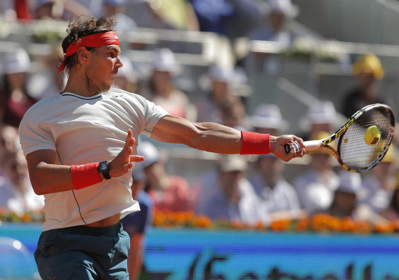 Rafael Nadal from Spain returns the ball to Stanislas Wawrinka from Switzerland during the men's final match at the Madrid Open tennis tournament, in Madrid, Sunday, May 12, 2013. (AP Photo/Andres Kudacki)