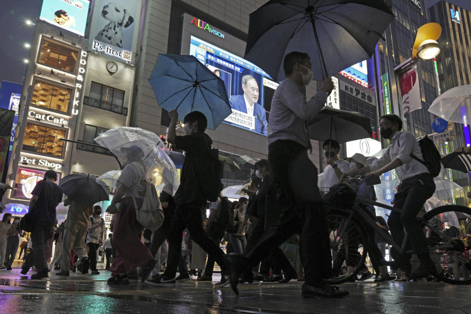 Pedestrians walk past a giant public TV with a live broadcast of a news conference by Japanese Prime Minister Yoshihide Suga after he announced a state of emergency because of rising coronavirus infections Thursday, July 8, 2021, in Tokyo. Suga said the state of emergency would go in effect on Monday and last through Aug. 22. This means the Olympics, opening on July 23 and running through Aug. 8, will be held entirely under emergency measures. The Paralympics open on Aug. 24. (AP Photo/Eugene Hoshiko)